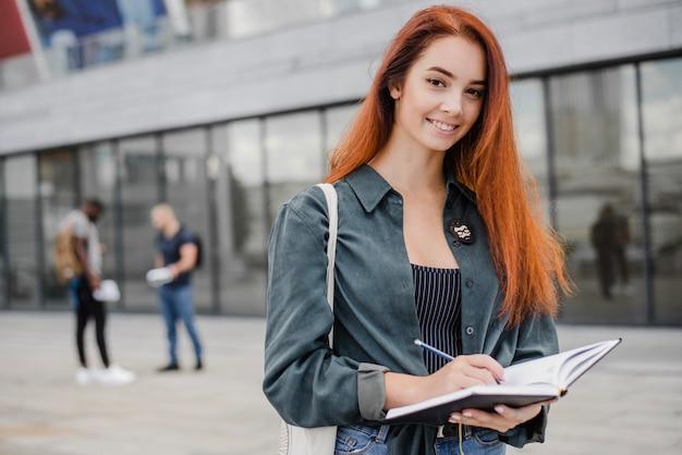 Sonriente mujer elegante con bloc de notas Foto Gratis