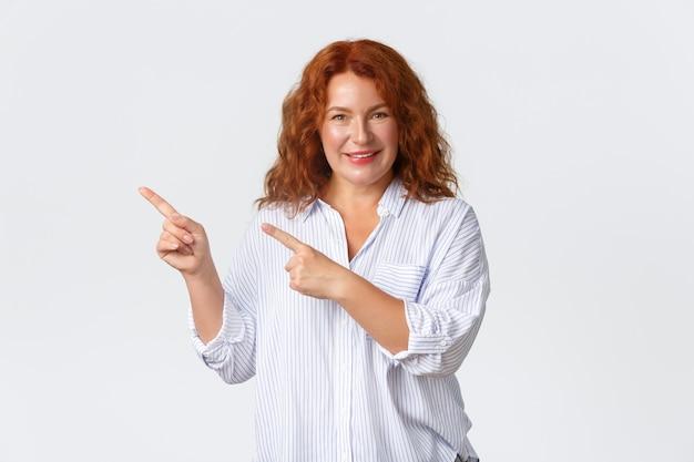 Sonriente mujer encantadora pelirroja de mediana edad que muestra el anuncio, señalando con el dedo la esquina superior izquierda. señora alegre con banner de producto de demostración de cabello jengibre sobre fondo blanco. Foto gratis