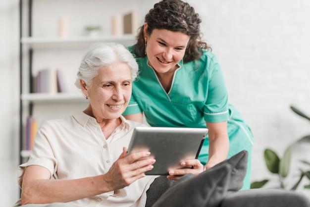 Sonriente mujer enfermera y su paciente mirando la pantalla de la tableta digital Foto Premium