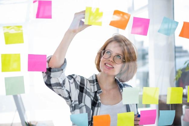 Sonriente mujer hipster pegar notas en un tablón de anuncios en la oficina Foto Premium
