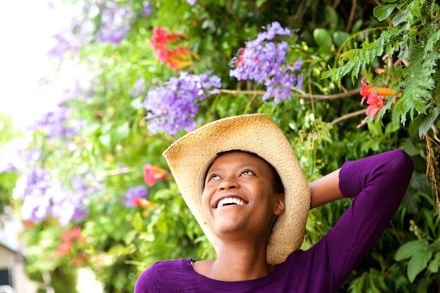 Sonriente mujer joven con sombrero de pie al aire libre  c6af3d7053b