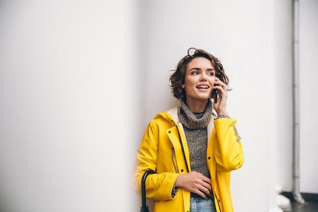 Sonriente mujer joven vestida con gabardina Foto gratis
