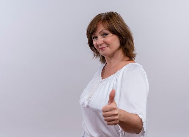 Sonriente mujer de mediana edad mostrando el pulgar hacia arriba en la pared blanca aislada Foto gratis