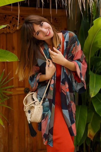 Sonriente mujer morena despreocupada en elegante traje de verano disfrutando de vacaciones en resort de lujo. jardín exótico con plantas tropicales. Foto gratis