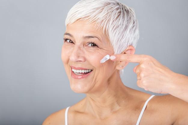 Sonriente mujer senior aplicando loción antienvejecimiento para eliminar las ojeras bajo los ojos. mujer madura con