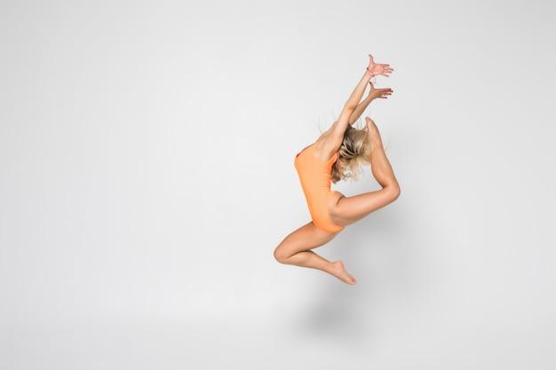 Sonriente niña gimnasta flexible en un traje haciendo ejercicios de estiramiento Foto gratis