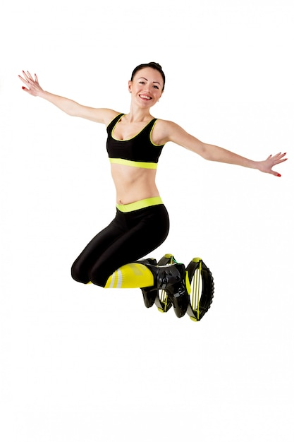 Sonriente niña morena saltando en un kangoo salta zapatos. Foto Premium