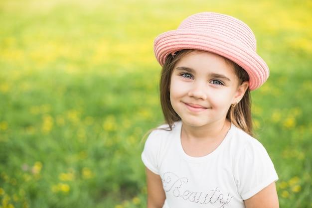 Sonriente niña con sombrero rosa en la cabeza en el parque Foto gratis