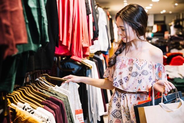 Sonriente niña en la tienda de ropa de elección Foto Premium