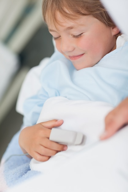 Sonriente niño acostado en una cama médica Foto Premium