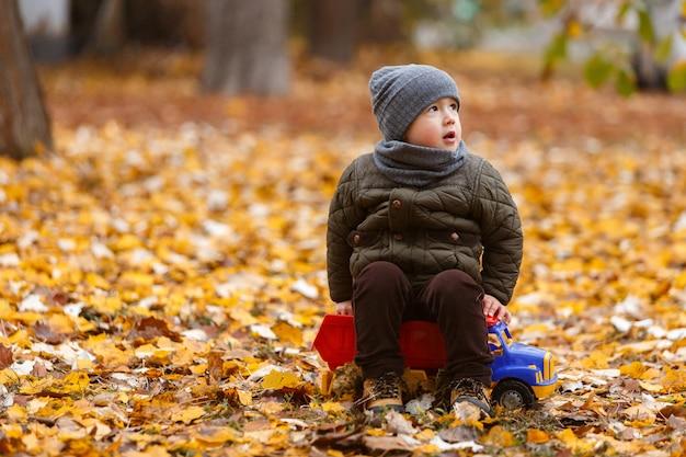 Sonriente niño caminando y jugando con el coche de juguete al aire libre en otoño. concepto de infancia feliz retrato de niño gracioso Foto Premium