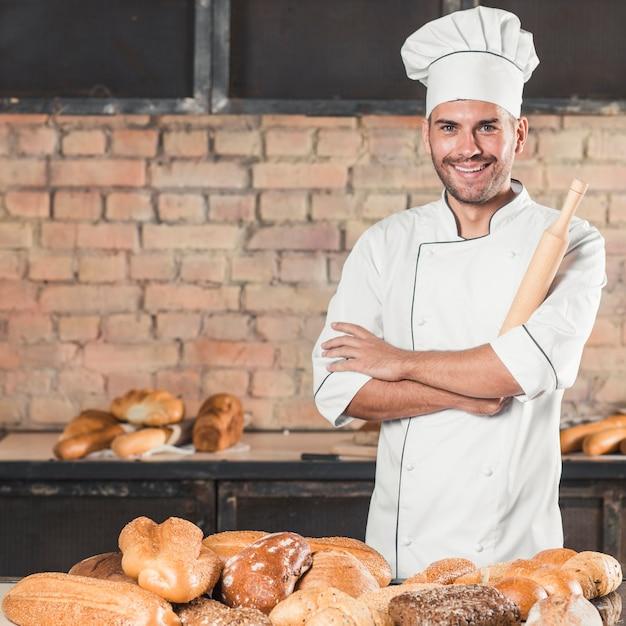 Sonriente panadero masculino con diferentes tipos de panes horneados en panadería Foto gratis