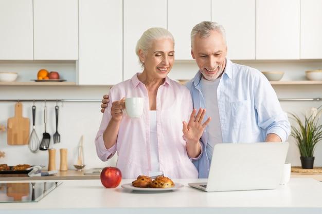Sonriente pareja amorosa madura familia comiendo pasteles mientras está usando la computadora portátil Foto gratis