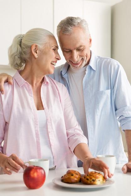 Sonriente pareja amorosa madura familia de pie en la cocina Foto gratis