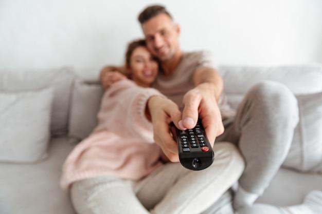 Sonriente pareja amorosa sentados juntos en el sofá y viendo la televisión. centrarse en el control remoto del televisor Foto gratis