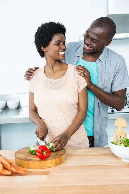 Sonriente pareja embarazada cortar verduras en la cocina en casa Foto Premium