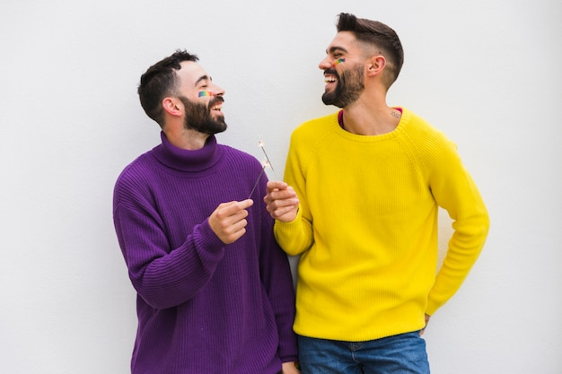 Sonriente pareja masculina con luces de bengala Foto gratis