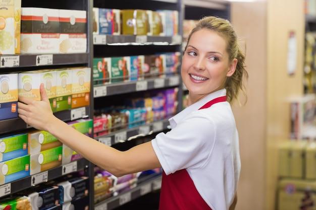 Sonriente rubia trabajador tomando un producto en estante Foto Premium