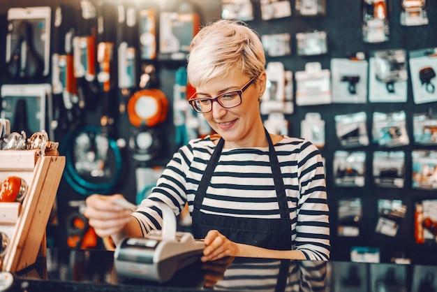 Sonriente trabajadora caucásica con cabello rubio corto y anteojos con caja registradora mientras está de pie en la tienda de bicicletas. Foto Premium