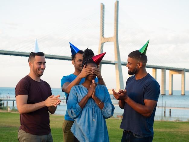 Sonrientes amigos haciendo sorpresa para mujer enfocada Foto gratis