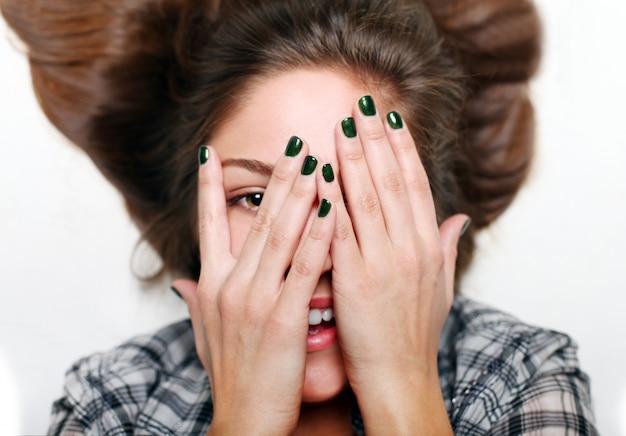 Sonrientes manos adolescentes de cara, arte de uñas verde Foto gratis