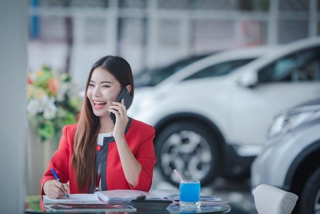Sonrientes vendedores asiáticos haciendo una llamada telefónica en el nuevo showroom de automóviles Foto Premium