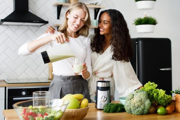 Sonrió atractiva mujer mulata en ropa de dormir y una mujer caucásica con batido saludable está de pie cerca de la mesa llena de frutas y verduras frescas en la cocina moderna blanca Foto gratis