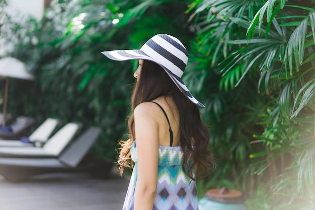 Sonrisa asiática joven hermosa de la mujer del retrato y feliz alrededor del jardín al aire libre Foto gratis