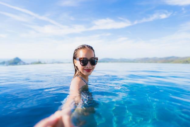 La sonrisa asiática joven hermosa de la mujer del retrato feliz se relaja alrededor de piscina en el centro turístico del hotel para el ocio Foto gratis