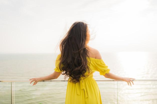La sonrisa asiática joven hermosa de la mujer del retrato feliz y se relaja en el balcón al aire libre con la playa y el oce del mar Foto gratis