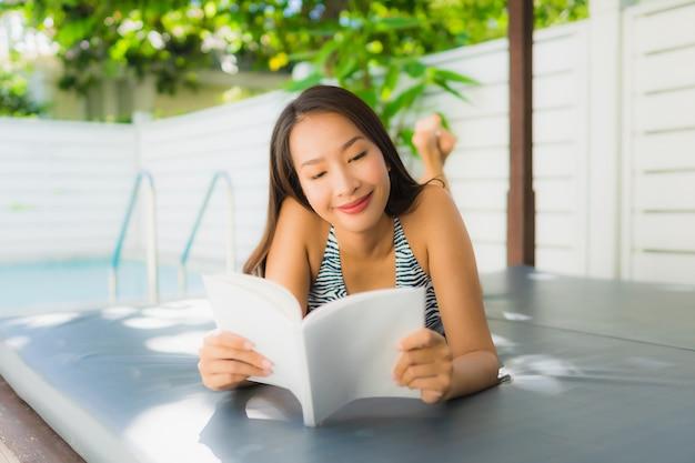 La sonrisa asiática joven hermosa de la mujer del retrato feliz se relaja con el libro de lectura alrededor de piscina Foto gratis