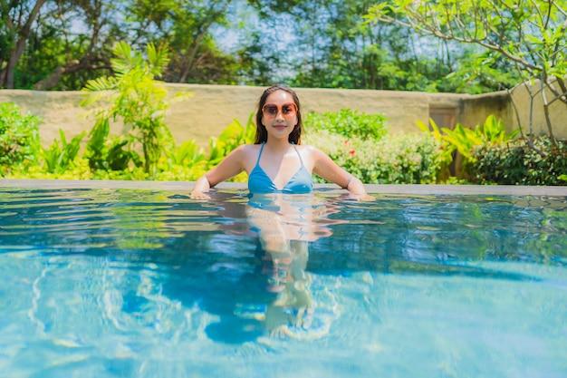 La sonrisa asiática joven hermosa de la mujer del retrato feliz se relaja y el ocio en la piscina Foto gratis