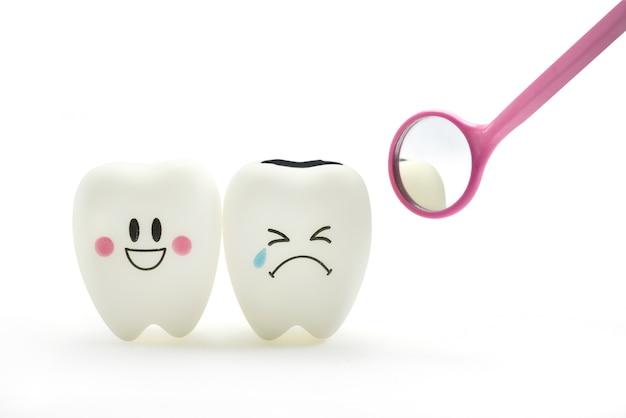 Sonrisa del diente y emoción del grito con el espejo dental en el fondo blanco. Foto Premium