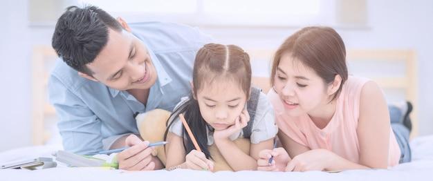 La sonrisa feliz de la familia asiática y se relaja en cama en casa. Foto Premium