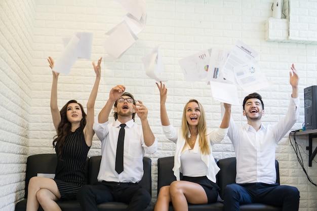 Sonrisa feliz gente de negocios, tirar papeles, documentos volar en el aire, con éxito con el trabajo. concepto de éxito empresarial. Foto Premium