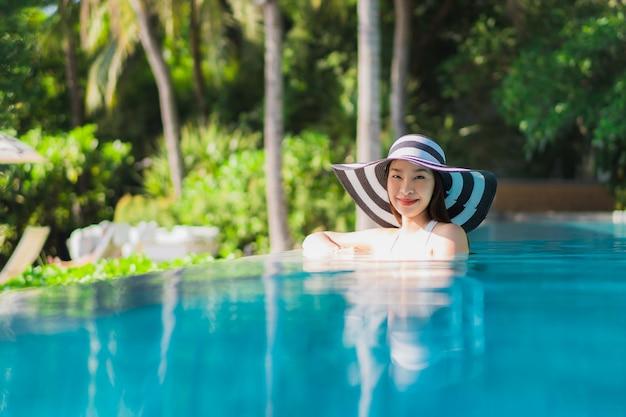 Sonrisa feliz de la mujer asiática joven hermosa del retrato en piscina alrededor del centro turístico y del hotel Foto gratis