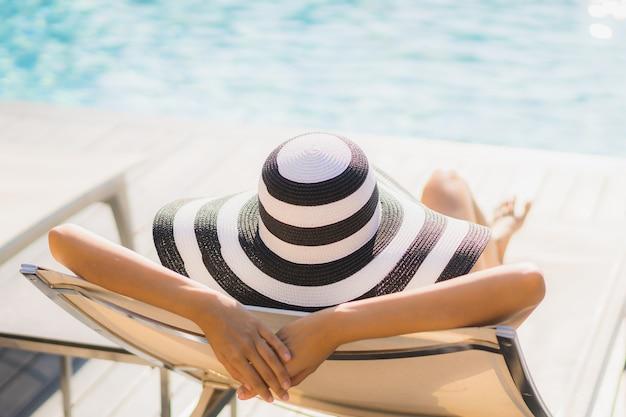 La sonrisa feliz de la mujer asiática joven hermosa del retrato y se relaja alrededor de piscina en centro turístico del hotel Foto gratis