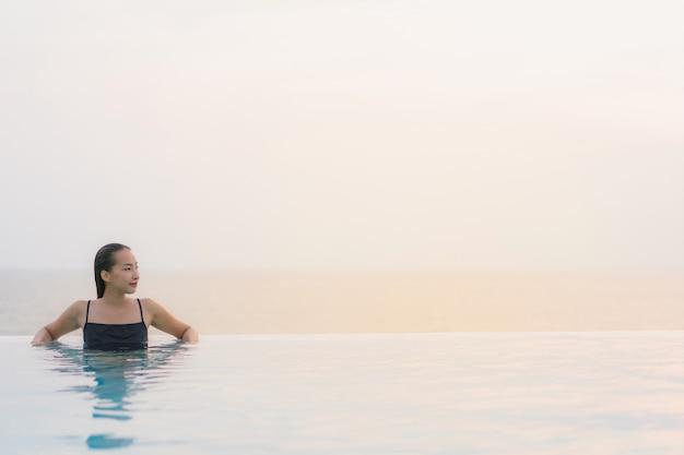 La sonrisa feliz de la mujer asiática joven hermosa del retrato se relaja alrededor de piscina en centro turístico del hotel Foto gratis