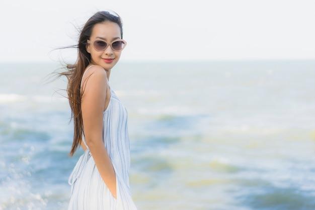 La sonrisa feliz de la mujer asiática joven hermosa del retrato se relaja alrededor de la playa y del mar neary Foto gratis