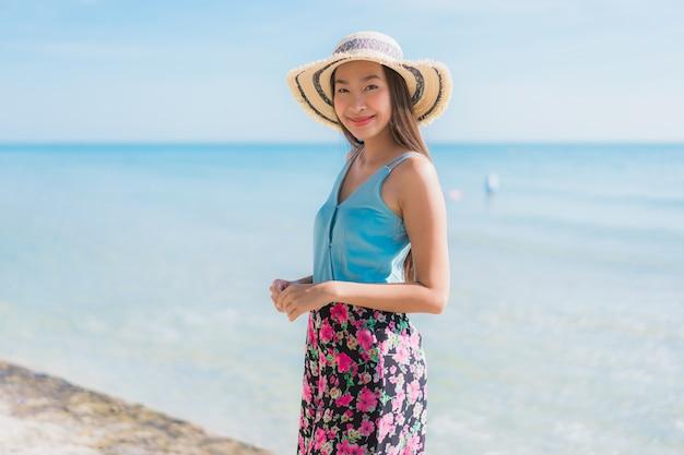 La sonrisa feliz de la mujer asiática joven hermosa del retrato se relaja alrededor de la playa océano y mar Foto gratis