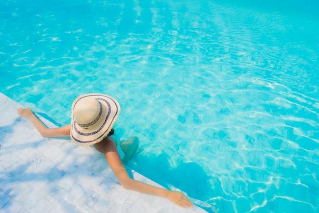 La sonrisa feliz de la mujer asiática joven hermosa del retrato se relaja en la piscina para las vacaciones del viaje Foto gratis