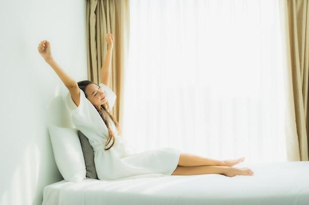 La sonrisa feliz de la mujer asiática joven se relaja en cama en dormitorio Foto gratis
