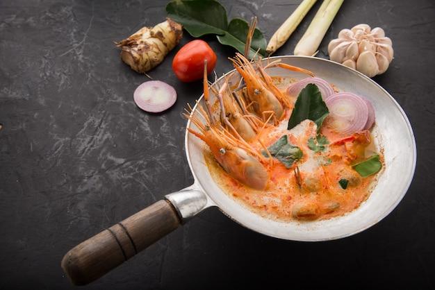 Sopa agridulce picante de tom yum goong en la vista superior de la mesa de madera Foto Premium