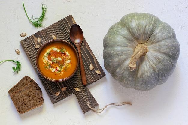Sopa asada de calabaza y zanahoria con crema, pimienta negra y semillas de calabaza, tabla de cortar y rodajas de calabaza fresca, pan negro Foto gratis