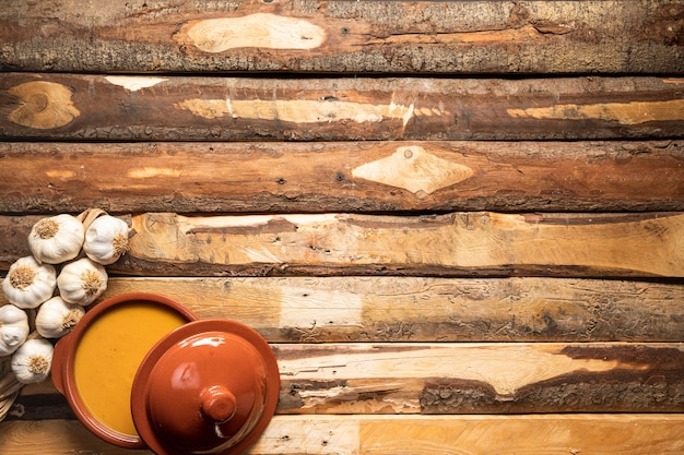 Sopa de calabaza y ajo planos sobre fondo de madera Foto gratis