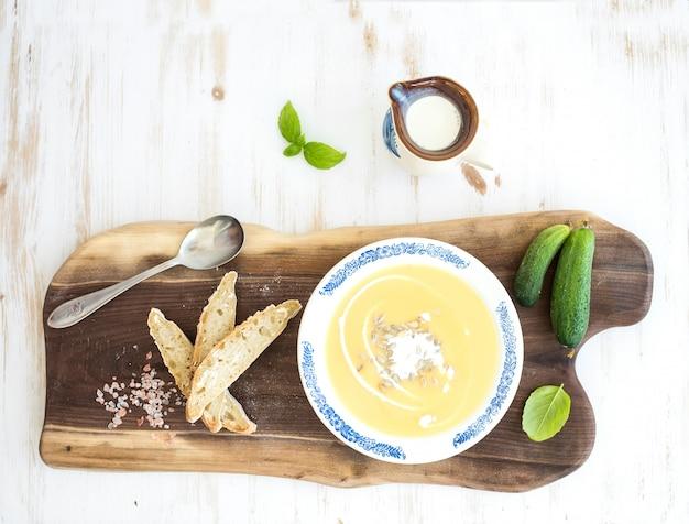 Sopa de calabaza con crema, albahaca fresca, pepinos y pan en plato de cerámica vintage sobre tabla de madera sobre fondo blanco, vista superior Foto Premium