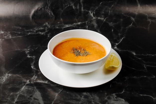 Sopa de calabaza dentro de un tazón blanco con hierbas y especias con una rodaja de limón alrededor. Foto gratis