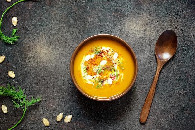 Sopa de calabaza y zanahoria asada con crema, semillas y verde fresco en un tazón de cerámica. vista superior Foto gratis