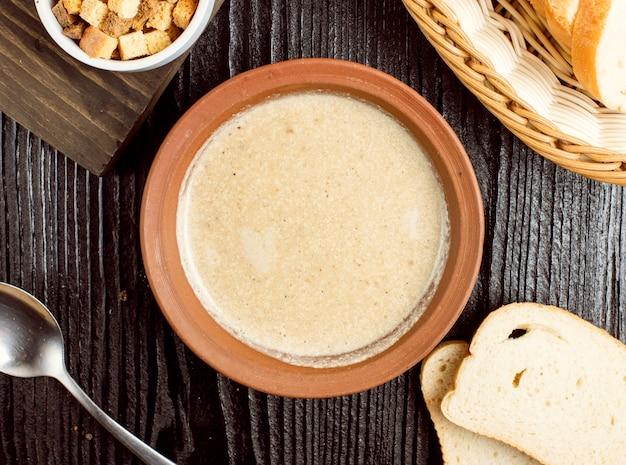 Sopa cremosa de champiñones en un tazón de cerámica con galletas de pan. Foto gratis
