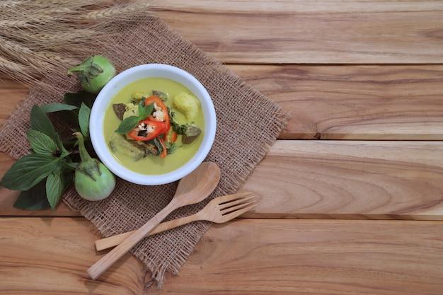Sopa de curry verde tailandés en una mesa de madera con ingredientes Foto Premium